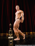 Picture of a body builder posing on stage with his trophy. The man is flexing his muscles for the audience. The man is wearing only a thong and is bare chested and bare foot.